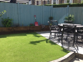 Makeover West Hampstead AFTER. Slate floor, sleeper planters and artificial lawn. Lovely!
